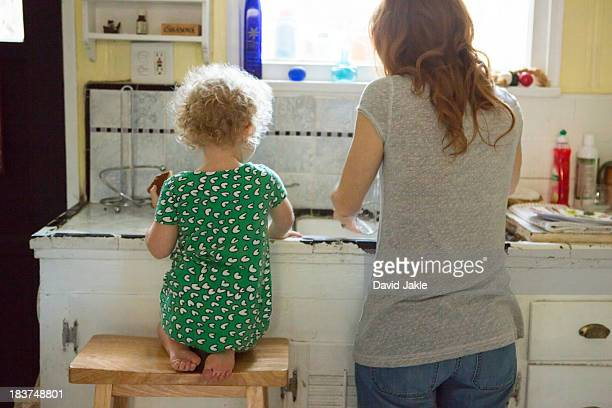 Mother and child at kitchen sink