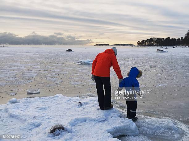 mother and child at lakeshore against sky during winter - helsinki foto e immagini stock