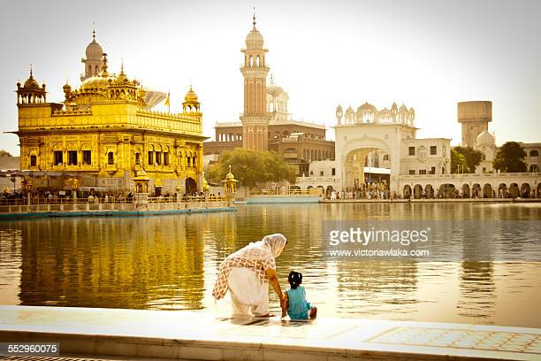 mother and child at the golden temple in amritsar - punjab india stock pictures, royalty-free photos & images