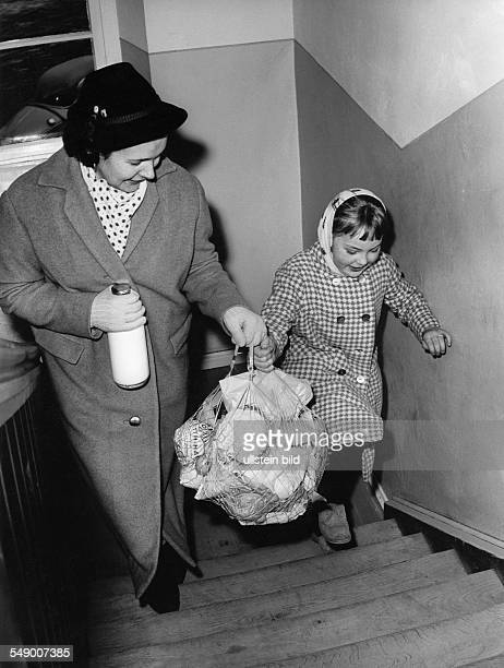 Mother and child back from shopping with heavy filled string bag lete fifties