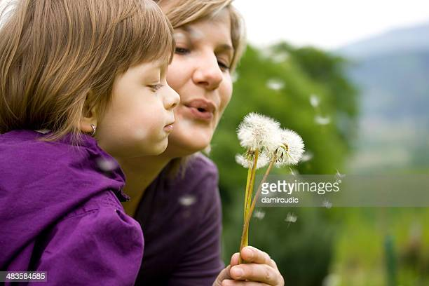 Mother and child blowing dandelion