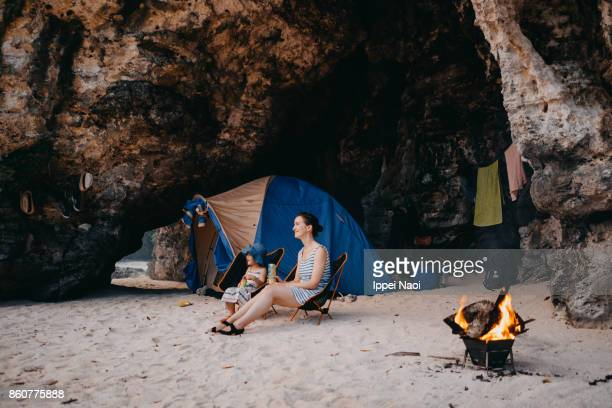 Mother and child camping in beach cave and watching sunset with campfire and tent, Japan