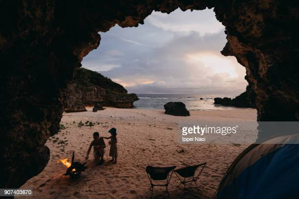 Mother and child camping inside cave on beach with campfire and tent, Japan