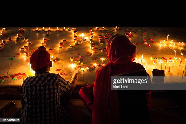 Mother and child celebrating Diwali festival night also Bandi Chhor Divas celebration for the Sikh religion followers at the Gurdwara Dukh Nivaran...