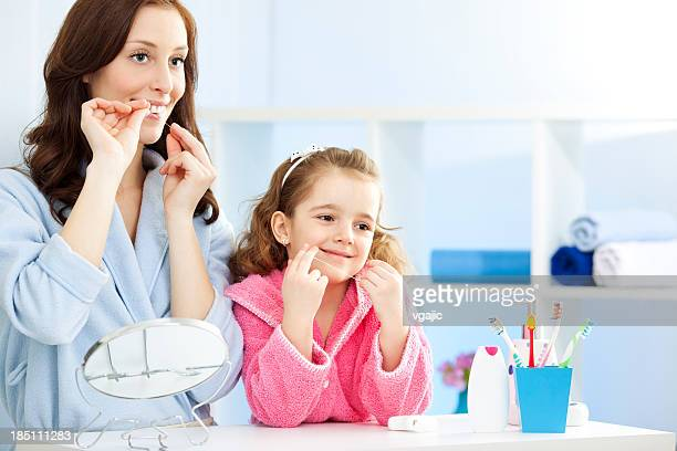 Mother and child dental flossing teeth together.