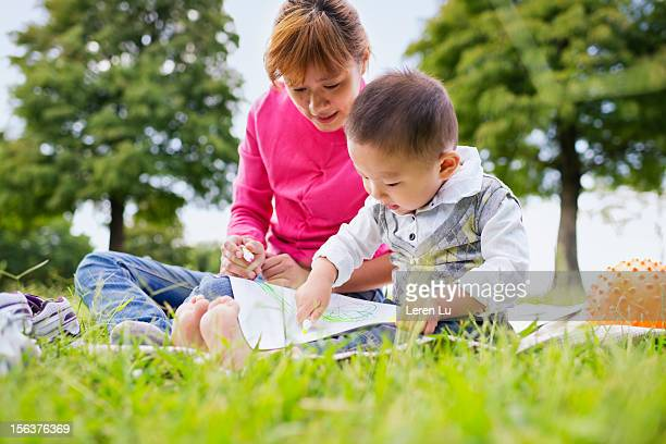 mother and child draw on paper outdoor - leren stock pictures, royalty-free photos & images