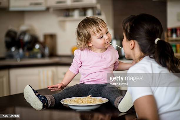 Mother and child eating spaghetti together