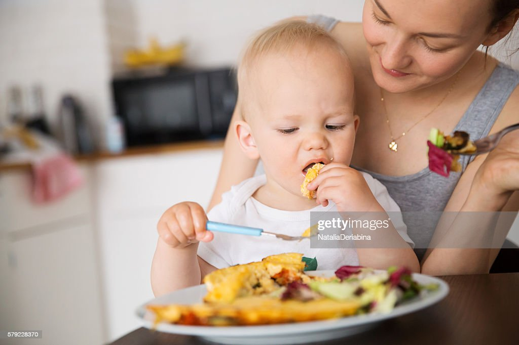 Mother and child eating together : Stock Photo