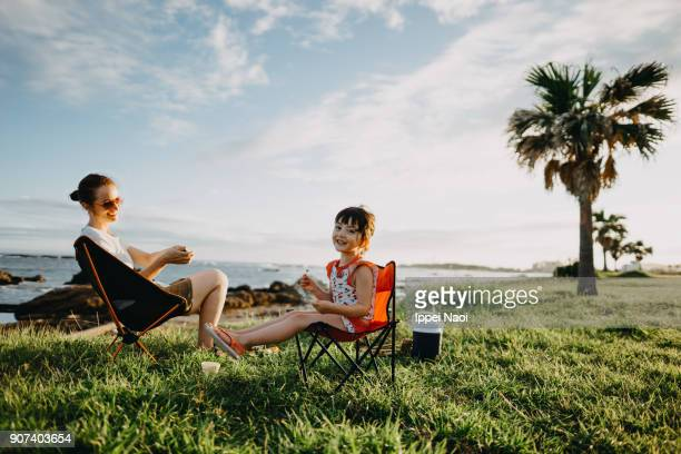 mother and child enjoying camping by the sea - buitensport stockfoto's en -beelden