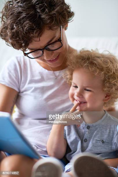 mother and child enjoying cartoons - cartoon characters with curly hair stock photos and pictures