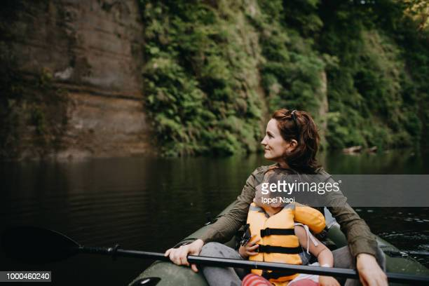 mother and child enjoying view from inflatable boat on river - kayaking stock pictures, royalty-free photos & images
