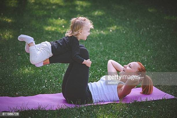 mother and child excersise outdoors. - physical education stock photos and pictures