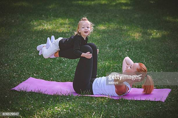 Mother and child excersise outdoors.
