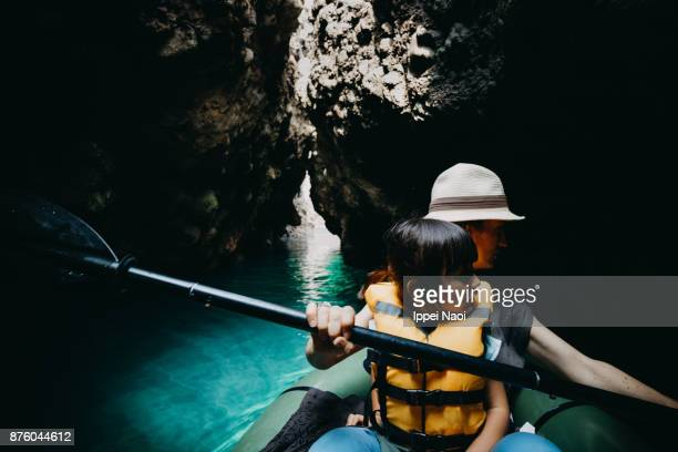 Mother and child exploring a sea cave by kayak