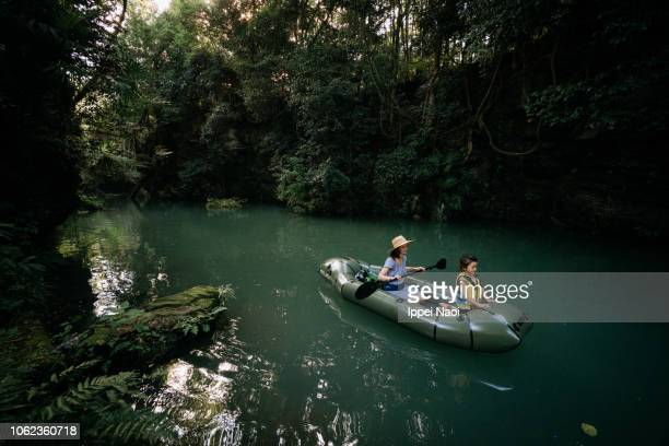 Mother and child exploring forest river by inflatable kayak, Japan