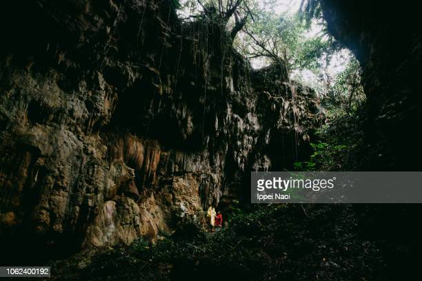 Mother and child exploring limestone cave in jungle, Okinawa, Japan