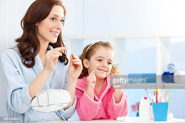 Mother and child flossing teeth together