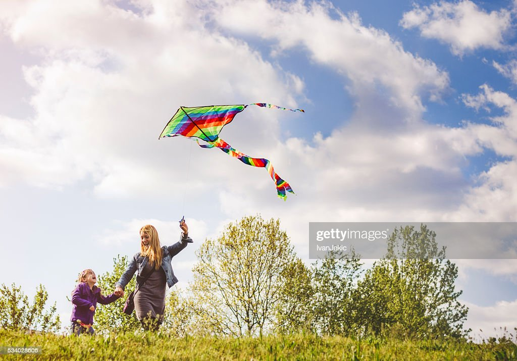 Mother and child flying kite together : Stock Photo
