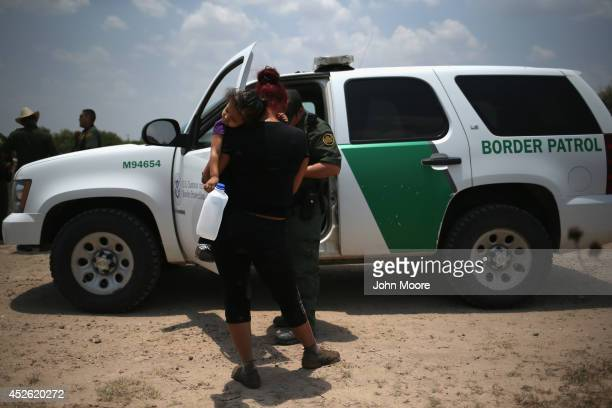 A mother and child from El Salvador await transport by the US Border Patrol to a processing center for undocumented immigrants after they crossed the...