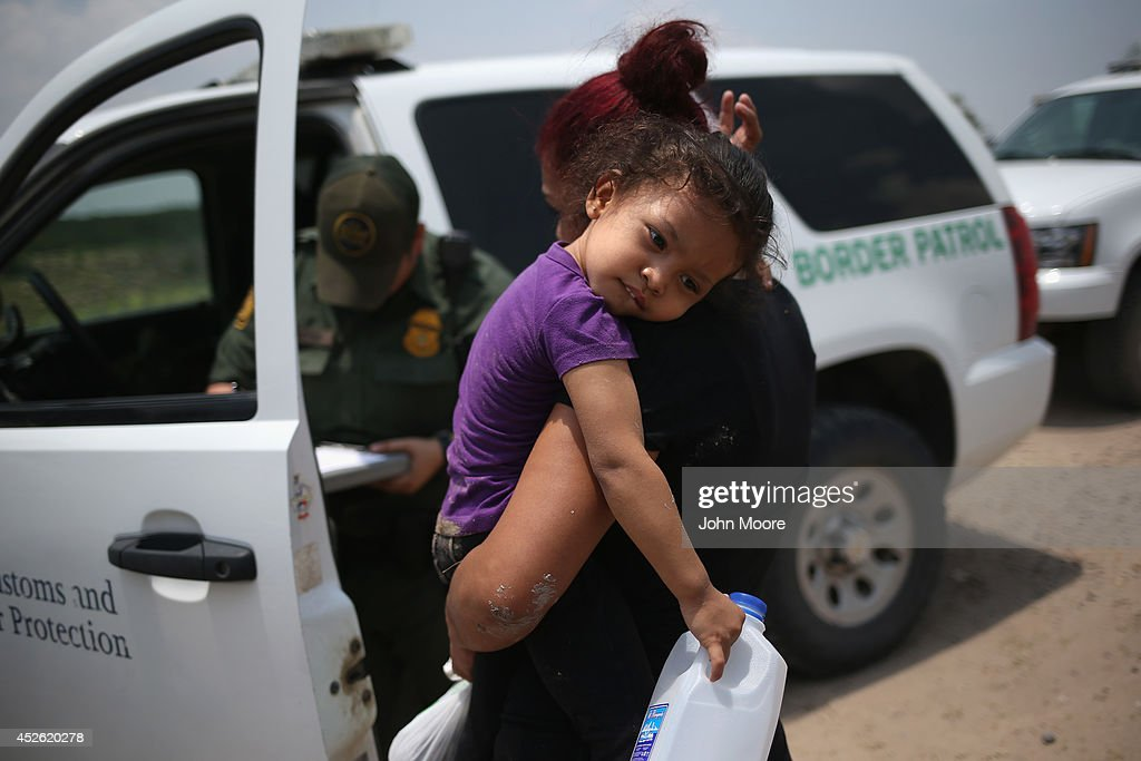 A mother and child, 3, from El Salvador await transport to a processing center for undocumented immigrants after they crossed the Rio Grande into the United States on July 24, 2014 in Mission, Texas. Tens of thousands of immigrant families and unaccompanied minors have crossed illegally into the United States this year and presented themselves to federal agents, causing a humanitarian crisis on the U.S.-Mexico border.