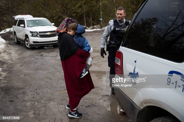 A mother and child from Turkey wait to be put into a police vehicle by the Royal Canadian Mounted Police after they crossed the USCanada border into...
