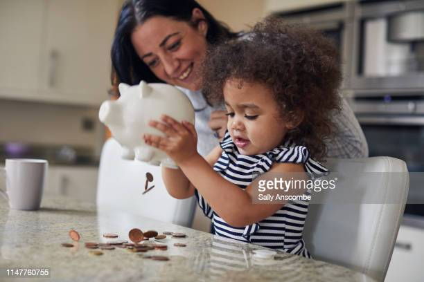 mother and child getting money from a piggy bank - business finance and industry stock pictures, royalty-free photos & images