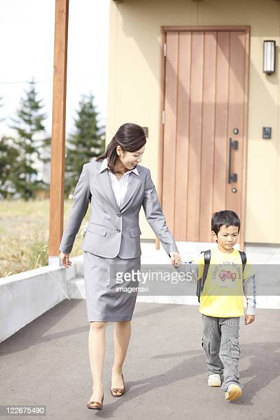Mother and child going out of front door