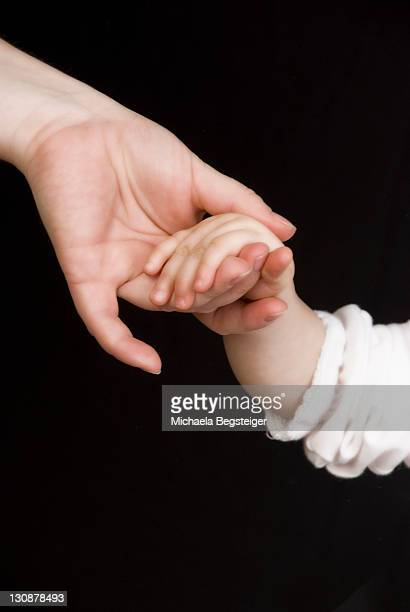 mother and child hand in hand - releasing stock photos and pictures