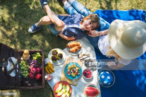 ピクニックをしている母子。covid-19危機の間に裏庭で楽しい - ピクニック ストックフォトと画像