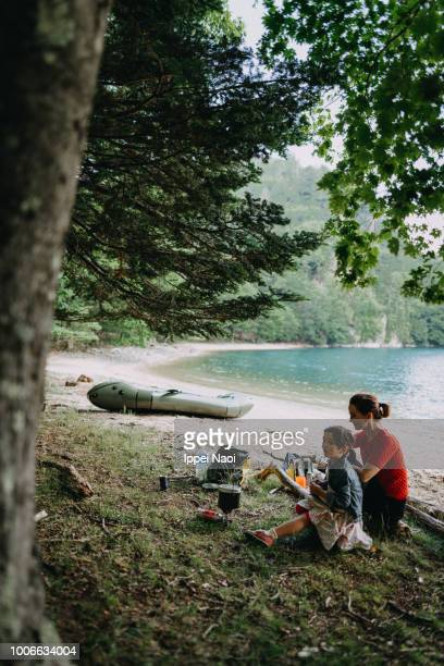 Mother and child having break on secluded lake beach during kayaking adventure