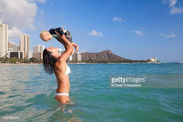 mother and child having fun at beach - waikiki stock pictures, royalty-free photos & images