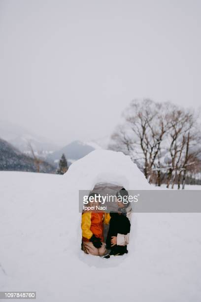 mother and child having fun in igloo on snowy mountain - igloo stock pictures, royalty-free photos & images