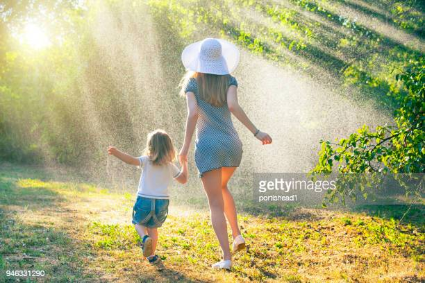mother and child having fun in the rain - mother son shower stock photos and pictures