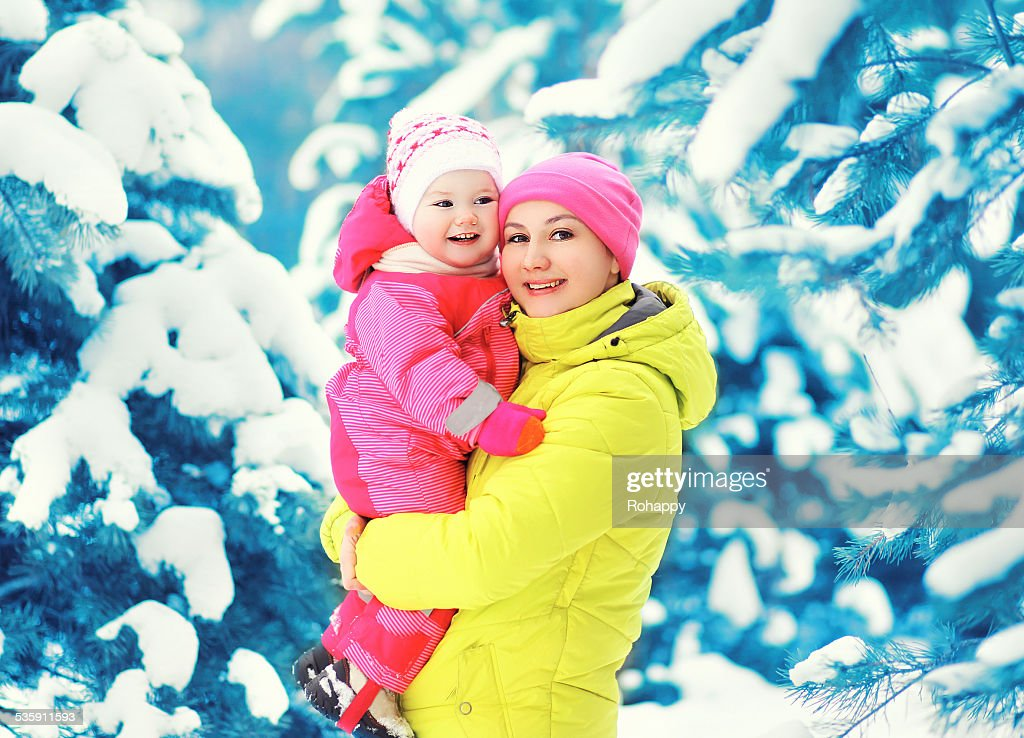 Mother and child having fun in winter snowy day : Stock Photo