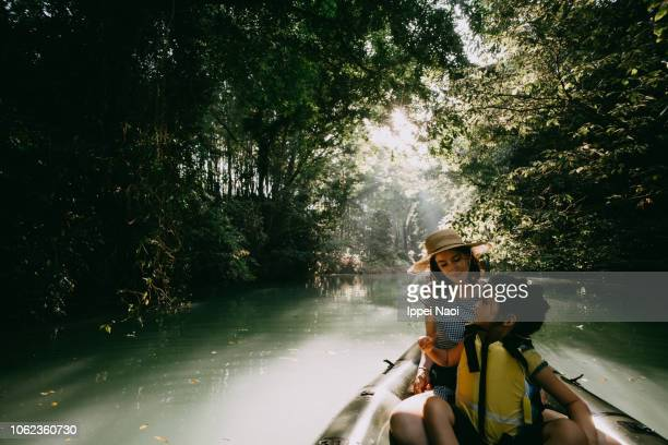 Mother and child having fun on inflatable boat on river in forest