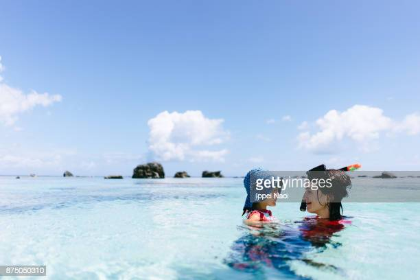 mother and child having intimate moment in clear tropical water, japan - family vacation stock pictures, royalty-free photos & images