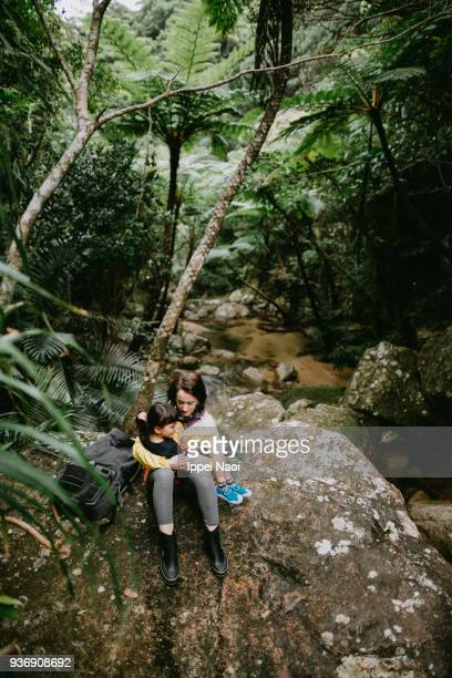 Mother and child having intimate moment in jungle, Okinawa, Japan