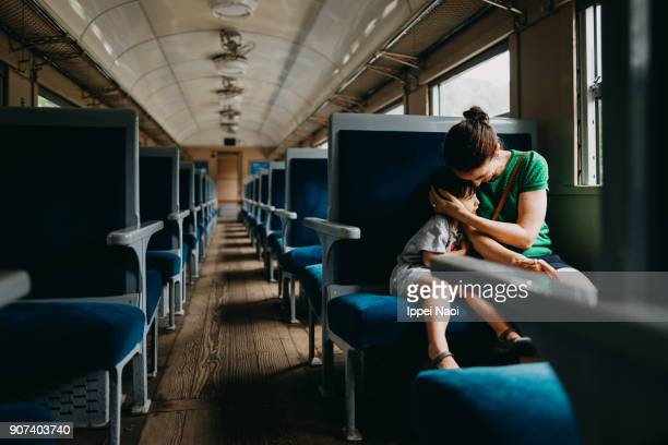 Mother and child having intimate moment in train