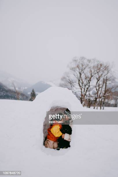 Mother and child having intimate moment inside igloo on snowy mountain