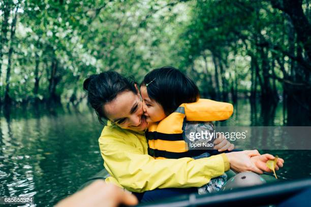 Mother and child having intimate moment while kayaking in jungle