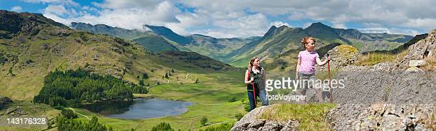 Mother and child hiking in idyllic mountain landscape