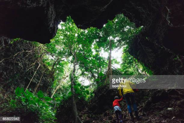 Mother and child hiking in jungle cave, Iriomote, Japan