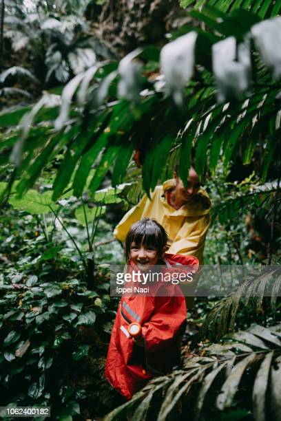 Mother and child hiking in jungle in rain, Okinawa, Japan