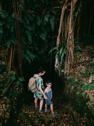 Mother and child hiking into cave covered by lush green vegetation - gettyimageskorea