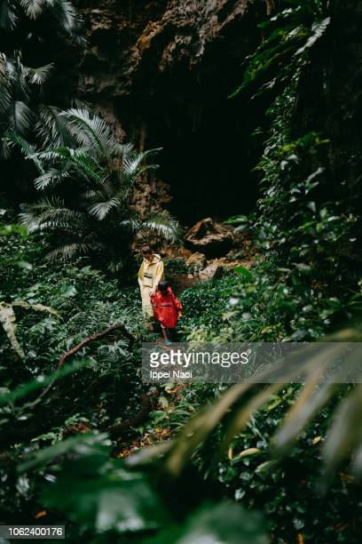 Mother and child hiking through jungle cave, Okinawa, Japan