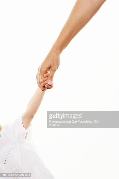 Mother and child (2-3) holding hands, close-up