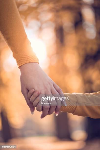Madre y el niño mantiene las manos en el parque público