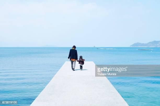 mother and child holding hands on pier - horizont über wasser stock-fotos und bilder