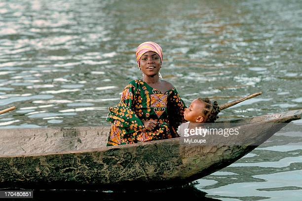 A mother and child in a dugout canoe in Ganvie a stilt village built on the waters of Lak Nokoue Benin West Africa