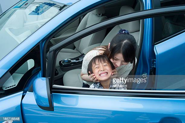 mother and child in electric car - landfahrzeug stock-fotos und bilder